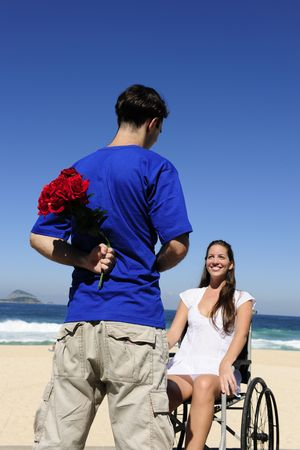 romantic surprise: man hiding red roses, a gift for his handicapped girlfriend  photo