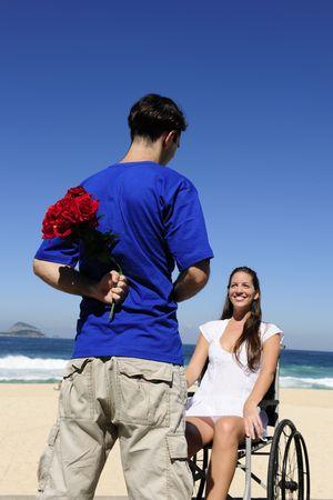 paraplegic: romantic surprise: man hiding red roses, a gift for his handicapped girlfriend