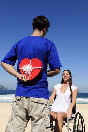 paraplegic: romantisch verbazing: man met een geschenk voor zijn gehandicapte girlfriend