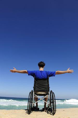 paraplegic: vacaciones de verano: hombre en silla de ruedas disfrutando al aire libre de playa