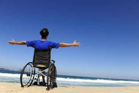 discapacitados: vacaciones de verano: hombre en silla de ruedas disfrutando al aire libre de playa