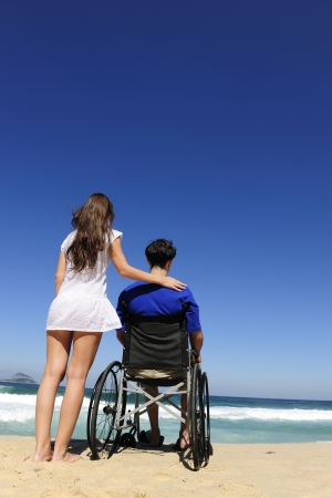 couple in love:  woman and husband in wheelchair on the beach photo