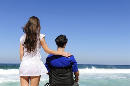 disability insurance: paio di amore: donna e il marito in sedia a rotelle sulla spiaggia
