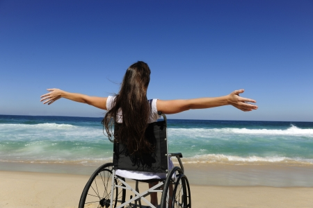 summer vacation: woman in wheelchair enjoying outdoors beach Stock Photo