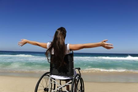 discapacitados: vacaciones de verano: mujer en silla de ruedas al aire libre disfrutando de playa