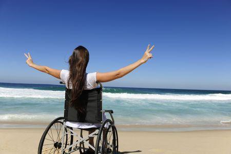 paraplegic: Happy gehandicapte vrouw in een rol stoel in de open lucht strand overwinning teken weer geven