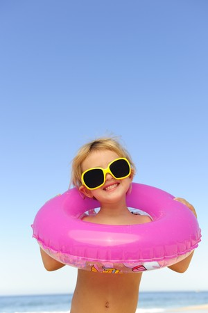 summer portrait: child with sunglasses and inflatable ring at the beach