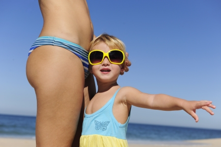 Summer vacation: Mother and daughter with sunglasses on the beach photo