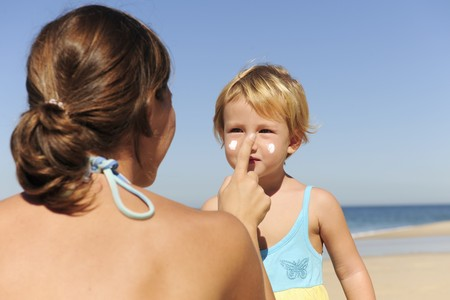 Suncare on the beach: Mother applying sunscream to her daughter photo
