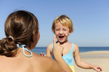 Suncare on the beach: Mother applying sunscream to her happy child photo