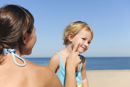 Suncare on the beach: Mother applying suntan lotion to her daughter photo