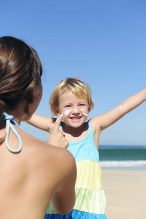 Suncare on the beach: Mother applying suncream to her happy child Stock Photo - 7309031