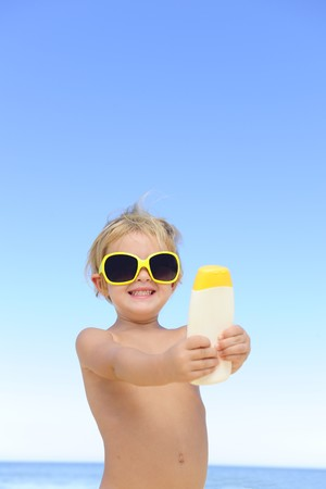 child with sunglasses showing suncream at the beach Stock Photo