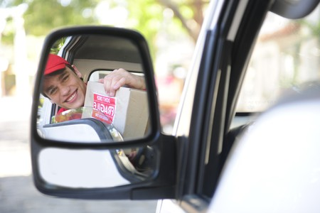 happy postal delivery courier in a van, rear view mirror perspective photo
