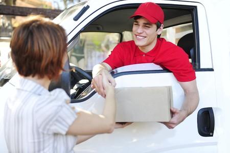 corriere: corriere consegna postale felice in un furgone che consegna il pacchetto e stretta di mano