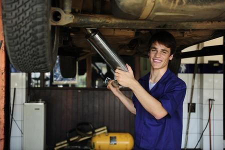 auto monteur: Gelukkig automonteur bij de auto reparatiewerkplaats  Stockfoto
