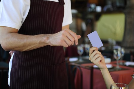 anonym: female customer paying with credit card at the restaurant Stock Photo