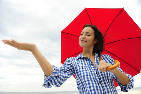 insurance: woman with red umbrella touching the rain photo