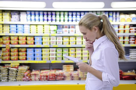 retailing: woman reading her shopping list in the supermarket with copy space