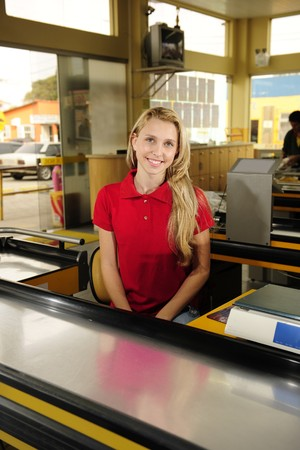Young woman working as a cashier at the supermarket photo