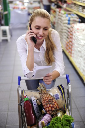 errand: Blond woman in the supermarket  talking on phone with shopping list