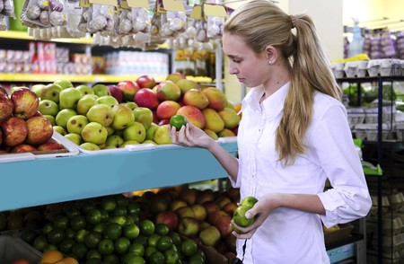 Woman shopping for fruits in the supermarket holding a lime photo