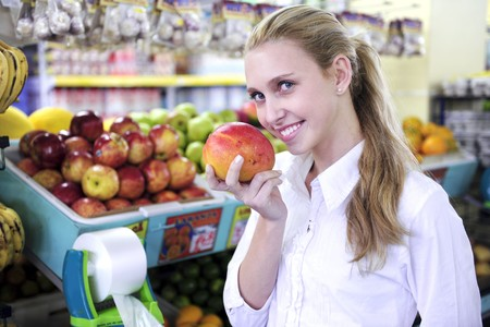 Happy blond woman smelling a mango in the supermarket photo