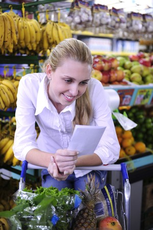 errand: blond woman reading her shopping list in the supermarket