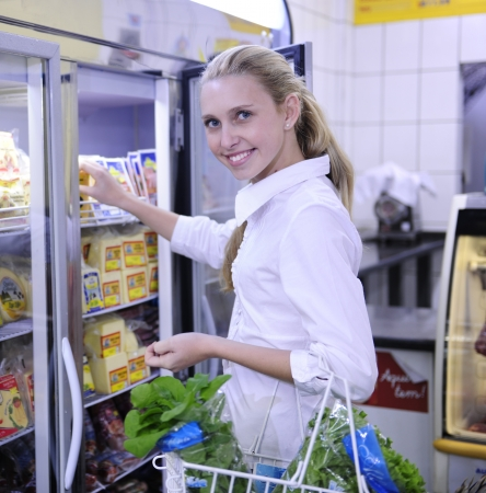 Blond woman shopping for frozen food in the supermarket photo