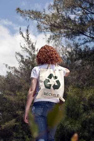 Sustainable lifestyle: Woman with recycling bad in nature photo