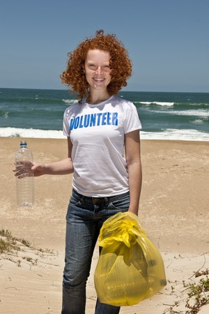 environmentalist: Young female volunteer collecting garbage on beach  Stock Photo