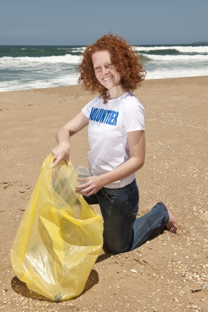 outreach: Young female volunteer collecting garbage on beach  Stock Photo