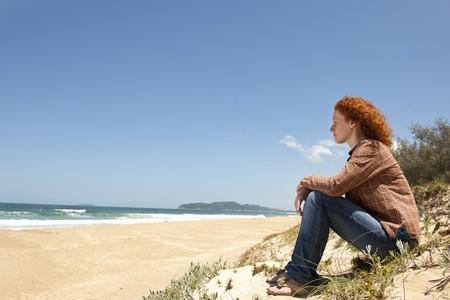 psicologia: pensativa mujer sentada sobre las dunas mirando el mar  Foto de archivo