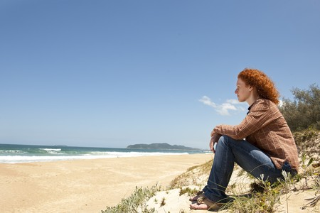 thoughtful woman: pensive woman sitting on the dunes watching the sea Stock Photo