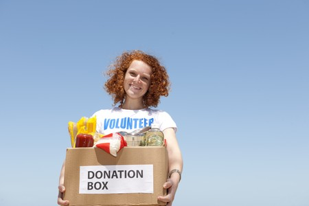 happy volunteer carrying food donation box Stock Photo
