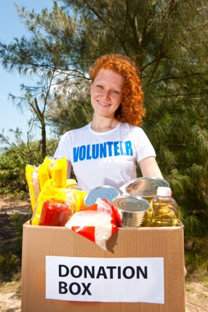 charitable: happy volunteer carrying food donation box Stock Photo