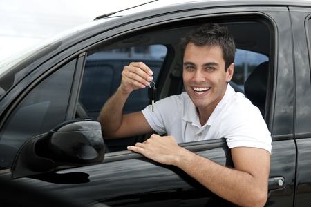 hire: Happy hispanic man showing the key of his new car