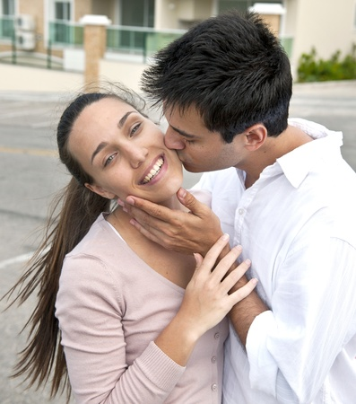 passionate kissing: hispanic couple in love: man kissing woman on cheek