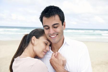 serene hispanic couple bonding on beach smiling photo