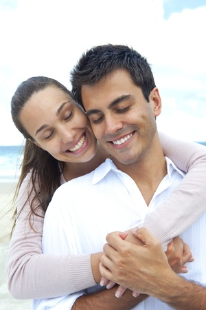 latin woman: happy couple in love daydreaming together on the beach Stock Photo