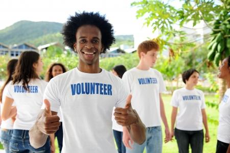 altruismo: hombre afroamericano voluntario feliz mostrando pulgares signo y grupo