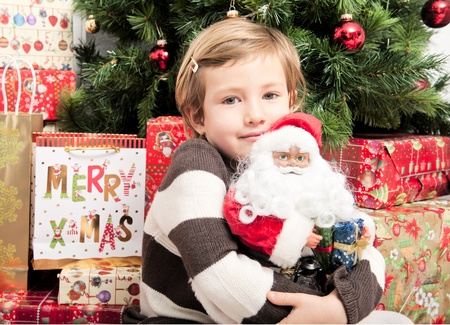 Cute child hugging santa doll in front of christmas tree photo