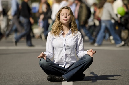 meditating woman: woman meditating yoga in lotus position on busy urban street