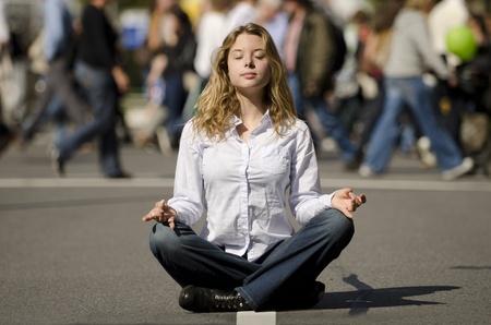 mujer meditando: yoga mujer meditando en posici�n de loto en la concurrida calle urbana
