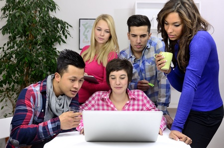 employees working: young diverse team of students or employees working Stock Photo