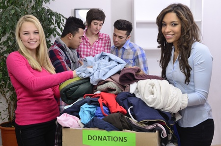 volunteering: young and diverse volunteer group with clothing donation