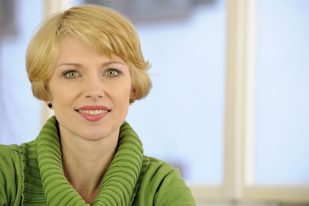 mature woman face: portrait of a woman wearing a green sweater with copyspace Stock Photo