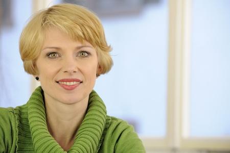 mujeres maduras: retrato de una mujer que llevaba un jersey verde con copyspace