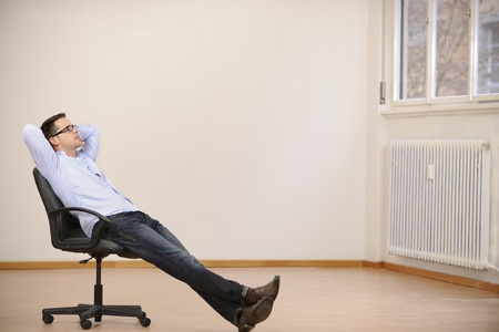 Businessman sitting alone in new new office  with copyspace photo