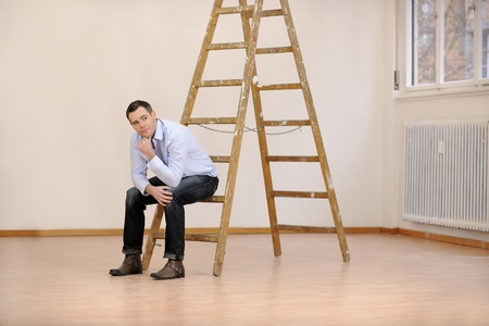property ladder: Moving to new office or house: man sitting on ladder in empty room